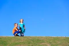 Petit garçon et fille regardant le ciel bleu Photos stock