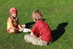Petit garçon et fille retenant un billet de banque Photographie stock
