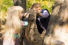 Petit garçon et fille riants jouant avec une porte Photographie stock