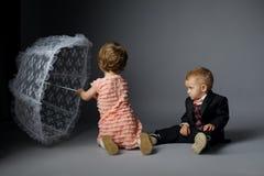 Petit garçon et fille s'asseyant sous le parapluie images libres de droits