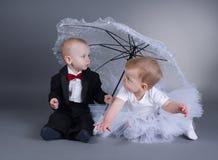 Petit garçon et fille s'asseyant sous le parapluie Image libre de droits