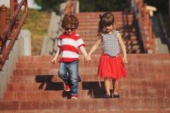 Petit garçon et fille sur l'escalier Photographie stock libre de droits