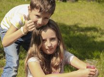 Petit garçon et fille sur la pelouse Photos stock