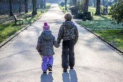 Petit garçon et fille tenant des mains et marchant un long chemin droit Photographie stock libre de droits