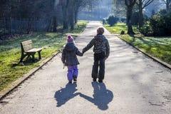 Petit garçon et fille tenant des mains et marchant un long chemin droit Images libres de droits
