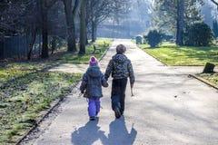 Petit garçon et fille tenant des mains et marchant un long chemin droit Image stock