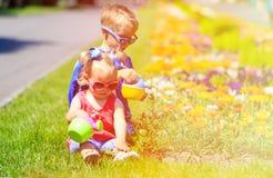 Petit garçon et fleurs de arrosage de fille d'enfant en bas âge dedans Photo libre de droits