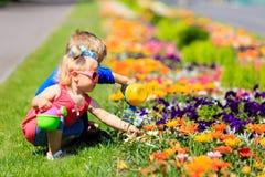 Petit garçon et fleurs de arrosage de fille d'enfant en bas âge en été Image stock