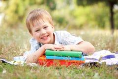 Petit garçon et livres dehors. De nouveau à l'école. Photographie stock