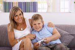 Petit garçon et mère jouant le sourire de jeu vidéo image stock