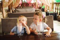 Petit garçon et milkshakes potables de fille dans un café dehors photos libres de droits