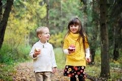 Petit garçon et petite fille mangeant des pommes dans la forêt Photographie stock