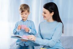 Petit garçon et sa mère collant des notes au carnet Photos libres de droits