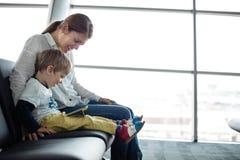 Petit garçon et sa mère s'asseyant dans un hall de départ d'aéroport Photos stock