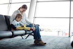 Petit garçon et sa mère s'asseyant dans un hall de départ d'aéroport Images libres de droits