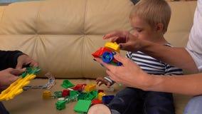 Petit garçon et ses parents jouant avec la construction réglée à la maison ensemble tir 4k clips vidéos