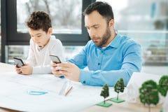 Petit garçon et son père étant collés à leurs téléphones Photos libres de droits