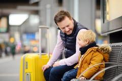 Petit garçon et son père attendant le train rapide sur la plate-forme de gare ferroviaire ou attendant leur vol à l'aéroport Photos libres de droits