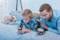 Petit garçon et son père se trouvant sur le lit utilisant des smartphones tandis que grand-papa photos libres de droits