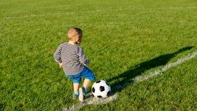 Petit garçon exécutant avec une bille de football Images stock