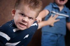 Petit garçon fâché brillant et combattant Images libres de droits