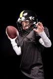 Petit garçon fâché dans l'uniforme jouant le football américain photographie stock libre de droits