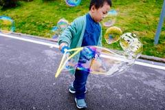 Petit garçon faisant des bulles de savon Photographie stock