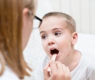 Petit garçon faisant examiner sa gorge par le professionnel de la santé photos libres de droits