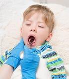 Petit garçon faisant examiner sa gorge par le professionnel de la santé images libres de droits