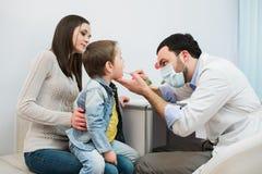 Petit garçon faisant examiner sa gorge par le professionnel de la santé photos stock