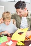 Petit garçon faisant les formes de papier avec le père à la table Images stock