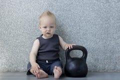 Petit garçon fatigué après pompage du fer avec un kettlebell se reposant sur le plancher Photographie stock