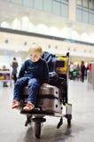 Petit garçon fatigué s'asseyant sur des valises sur l'aéroport international Images stock