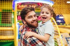 Petit garçon gai ayant l'amusement avec son papa image libre de droits