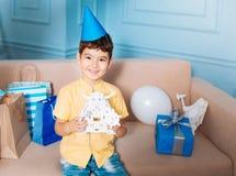 Petit garçon gai dans le chapeau de partie posant avec le robot de jouet Images stock