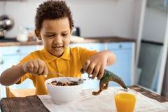 Petit garçon gai donnant la nourriture à son dinosaure de jouet Photos stock