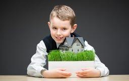 Petit garçon gardant le modèle de maison photographie stock