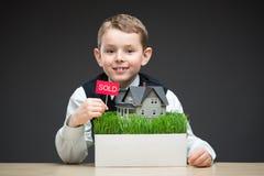 Petit garçon gardant le modèle de maison et le comprimé vendu images stock
