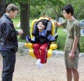 Petit garçon handicapé balançant dans l'oscillation d'handicap Photographie stock