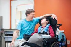 Petit garçon handicapé dans le fauteuil roulant parlant avec le père dans le hospita Photos libres de droits