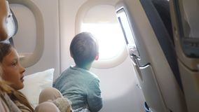 Petit garçon heureux appréciant la vue du siège fenêtre d'avion pendant le vol allant au voyage de vacances ainsi que la famille banque de vidéos