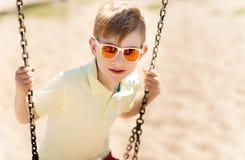 Petit garçon heureux balançant sur l'oscillation au terrain de jeu Images libres de droits
