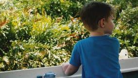 Petit garçon heureux d'ans 4-6 dans la navigation de bateau de visite de safari le long de la belle rivière exotique de jungle av banque de vidéos