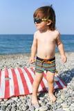 Petit garçon heureux dans des lunettes de soleil sur la plage en pierre Image libre de droits