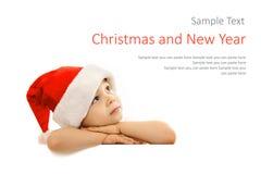 Petit garçon heureux dans le chapeau de Santa jetant un coup d'oeil par derrière Photos libres de droits