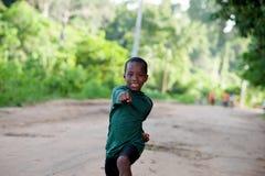 Petit garçon heureux dans les vêtements de sport faisant l'exercice en nature image stock