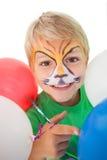 Petit garçon heureux en peinture de visage de tigre avec des ballons Photos libres de droits