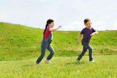 Petit garçon heureux et fille courant dehors Image libre de droits