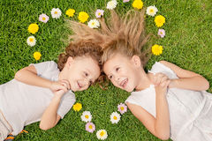 Petit garçon heureux et fille se trouvant sur l'herbe Images libres de droits