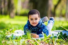 Petit garçon heureux mignon se situant dans l'herbe verte le ressort photographie stock